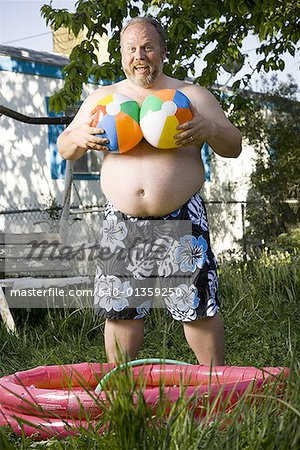 Overweight man by inflatable wading pool Stock Photo - Premium Royalty-Free, Image code: 640-01359250