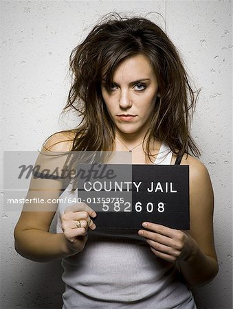 Mug shot of disheveled woman Stock Photo - Premium Royalty-Free, Image code: 640-01359735