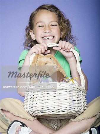 Portrait of a girl holding Easter eggs in a wicker basket Stock Photo - Premium Royalty-Free, Image code: 640-01359845