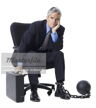 Businessman shackled to ball and chain Stock Photo - Premium Royalty-Free, Image code: 640-01360418