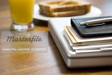 Close-up of laptop daytimer and papers on desk Stock Photo - Premium Royalty-Free, Image code: 640-01360528