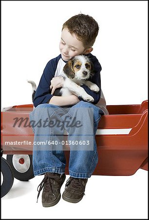 Close-up of a boy sitting on a wagon hugging a puppy Stock Photo - Premium Royalty-Free, Image code: 640-01360603