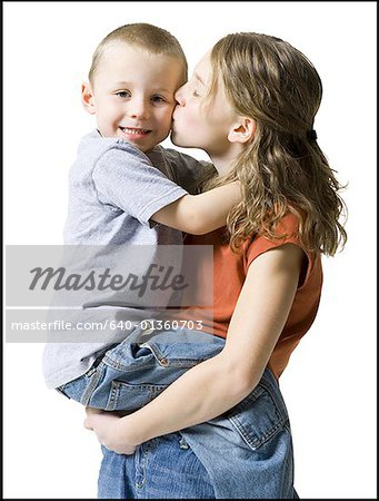 Profile of a sister kissing her brother Stock Photo - Premium Royalty-Free, Image code: 640-01360703