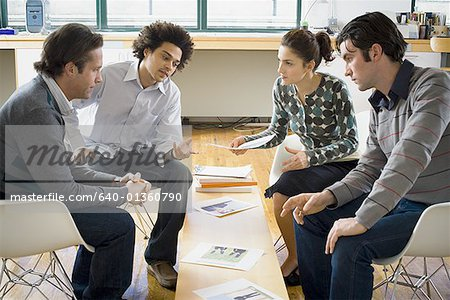 Four people discussing ad layouts Stock Photo - Premium Royalty-Free, Image code: 640-01360790