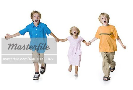 Portrait of two brothers running with their sister Stock Photo - Premium Royalty-Free, Image code: 640-01360877