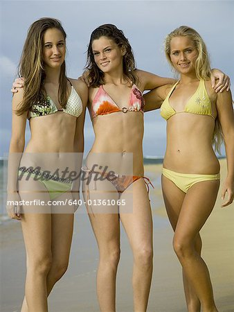 Portrait of three teenage girls with their hands on their shoulders Stock Photo - Premium Royalty-Free, Image code: 640-01361065