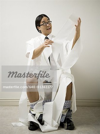 Close-up of a young man sitting on a toilet Stock Photo - Premium Royalty-Free, Image code: 640-01361177