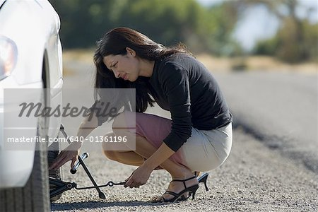Profile of a woman fixing a flat tire Stock Photo - Premium Royalty-Free, Image code: 640-01361196