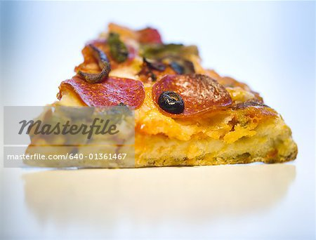 Close-up of a slice of pizza Stock Photo - Premium Royalty-Free, Image code: 640-01361467