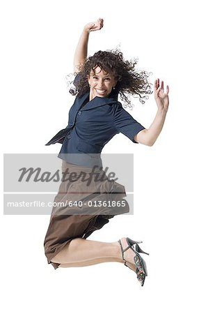 A young woman jumping with her arms raised Stock Photo - Premium Royalty-Free, Image code: 640-01361865