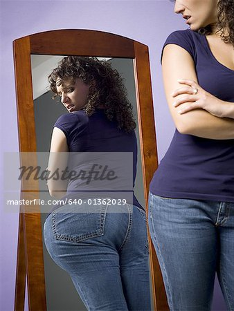 Young woman looking at her buttocks in the mirror Stock Photo - Premium Royalty-Free, Image code: 640-01362029