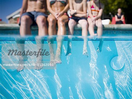 Feet dangling in swimming pool Stock Photo - Premium Royalty-Free, Image code: 640-01362050