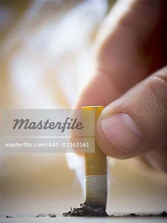 Close-up of a man putting out a cigarette Stock Photo - Premium Royalty-Free, Image code: 640-01362161