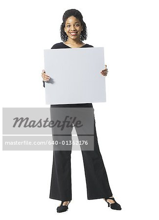 Portrait of a teenage girl holding a blank sign Stock Photo - Premium Royalty-Free, Image code: 640-01362176
