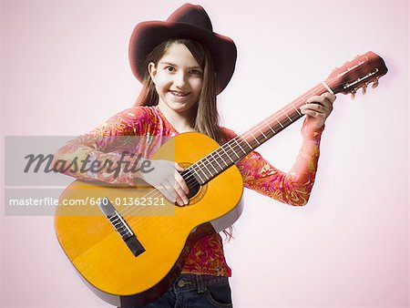 Portrait of a teenage girl playing the guitar Stock Photo - Premium Royalty-Free, Image code: 640-01362321