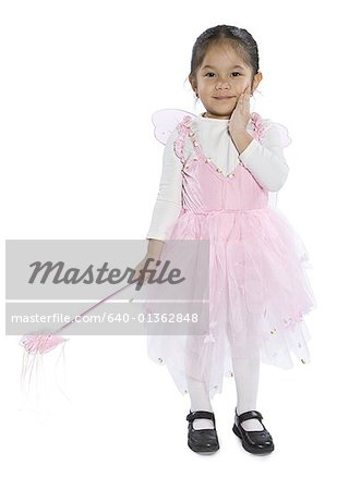 Portrait of a girl dressed up in a fairy costume holding a magic wand Stock Photo - Premium Royalty-Free, Image code: 640-01362848