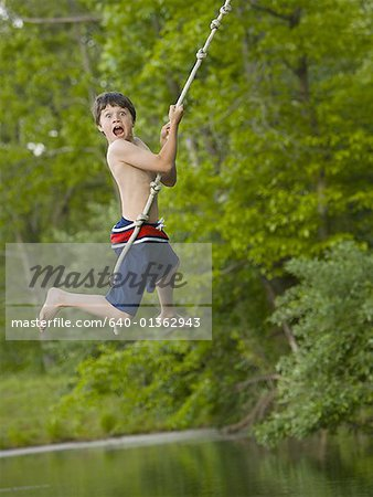 Portrait of a boy swinging on a rope Stock Photo - Premium Royalty-Free, Image code: 640-01362943
