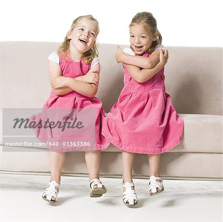 Two girls sitting side by side on a couch Stock Photo - Premium Royalty-Free, Image code: 640-01363386
