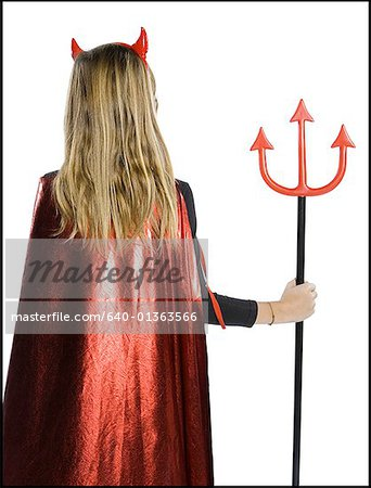 Rear view of a teenage girl wearing a devil costume holding a pitchfork Stock Photo - Premium Royalty-Free, Image code: 640-01363566