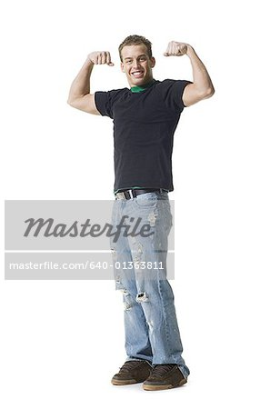 Portrait of a young man flexing muscles Stock Photo - Premium Royalty