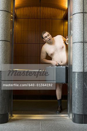 Naked businessman standing in an elevator and holding a briefcase Stock Photo - Premium Royalty-Free, Image code: 640-01364192