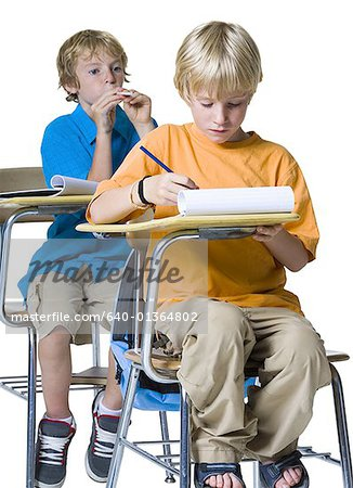Boy shooting a spitball at another boy Stock Photo - Premium Royalty-Free, Image code: 640-01364802
