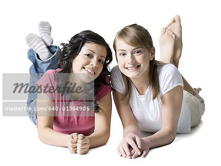 Portrait of two girls lying on the floor Stock Photo - Premium Royalty-Free, Image code: 640-01364905