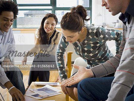 Four people discussing ad layouts Stock Photo - Premium Royalty-Free, Image code: 640-01365063