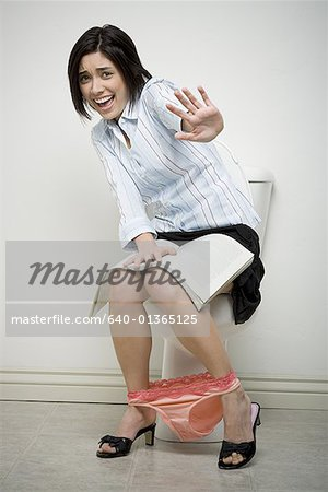 Portrait of a businesswoman sitting on a toilet making a stop gesture Stock Photo - Premium Royalty-Free, Image code: 640-01365125