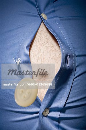 Close-up of fat stomach bursting through shirt Stock Photo - Premium Royalty-Free, Image code: 640-01365688