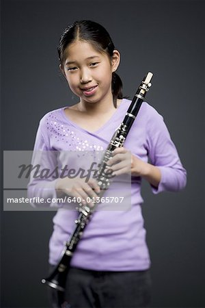 Portrait of a teenage girl holding a clarinet Stock Photo - Premium Royalty-Free, Image code: 640-01365707