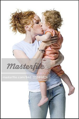 Close-up of a young woman kissing her daughter Stock Photo - Premium Royalty-Free, Image code: 640-01365826