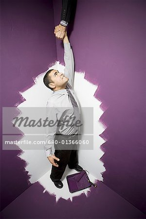 High angle view of a businessman reaching out for a man's hand Stock Photo - Premium Royalty-Free, Image code: 640-01366060