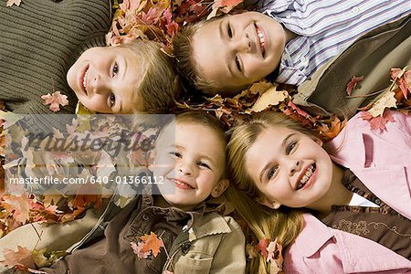 Young kids playing in a pile of fallen leaves Stock Photo - Premium Royalty-Free, Image code: 640-01366112