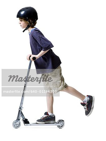 Profile of a boy riding on scooter Stock Photo - Premium Royalty-Free, Image code: 640-01366303