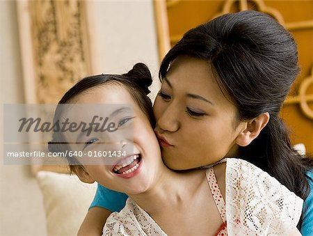 Mother giving daughter a kiss on cheek Stock Photo - Premium Royalty-Free, Image code: 640-01601434