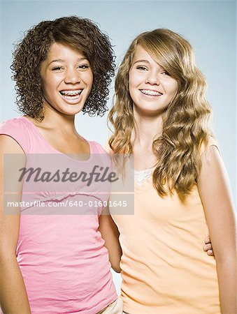 Two girls with braces embracing and smiling