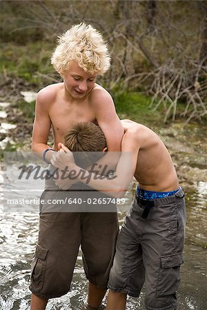 two boys playing in a river. Stock Photo - Premium Royalty-Free, Image code: 640-02657489