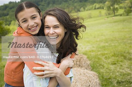 Portrait of a girl hugging her mother from behind Stock Photo - Premium Royalty-Free, Image code: 640-02764693