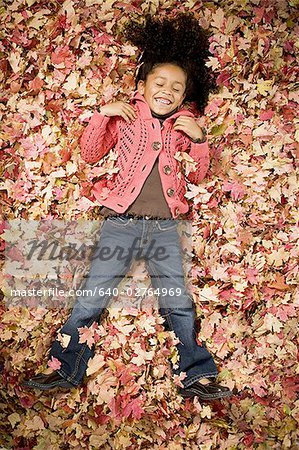 Young girl playing in fallen leaves Stock Photo - Premium Royalty-Free, Image code: 640-02764969