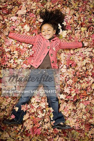 Young girl playing in fallen leaves Stock Photo - Premium Royalty-Free, Image code: 640-02764971