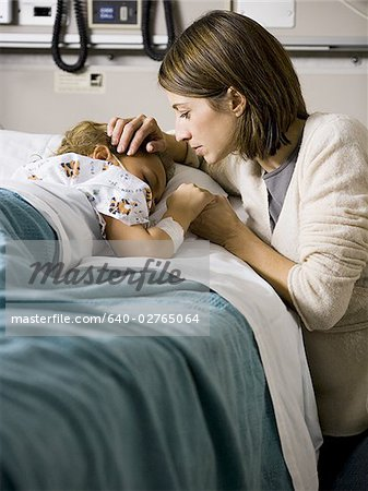 Woman kissing hand of young girl in hospital Stock Photo - Premium Royalty-Free, Image code: 640-02765064