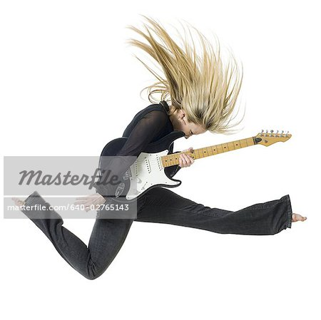 Profile of woman jumping with electric guitar Stock Photo - Premium Royalty-Free, Image code: 640-02765143