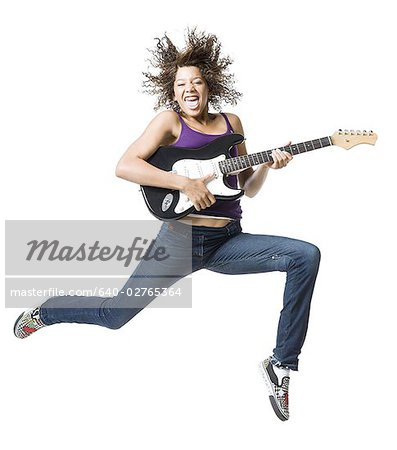 Girl with braces and guitar leaping and sticking tongue out Stock Photo - Premium Royalty-Free, Image code: 640-02765364