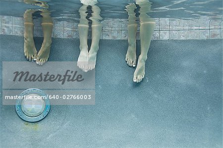 Low section view of three teenage girls feet in a swimming pool Stock Photo - Premium Royalty-Free, Image code: 640-02766003