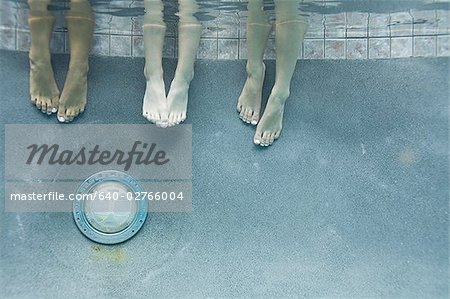 Low section view of three teenage girls feet in a swimming pool Stock Photo - Premium Royalty-Free, Image code: 640-02766004