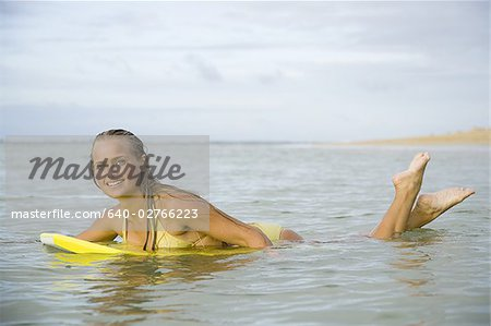 Portrait of a teenage girl floating on a boogie board in the sea Stock Photo - Premium Royalty-Free, Image code: 640-02766223