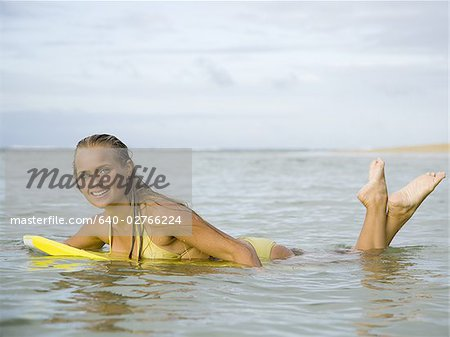Portrait of a teenage girl floating on a boogie board in the sea Stock Photo - Premium Royalty-Free, Image code: 640-02766224