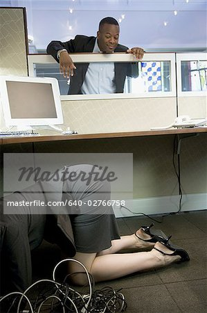 Businesswoman crouching under a computer desk with a businessman looking at her Stock Photo - Premium Royalty-Free, Image code: 640-02766758