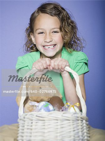 Portrait of a girl holding Easter eggs in a wicker basket Stock Photo - Premium Royalty-Free, Image code: 640-02766975